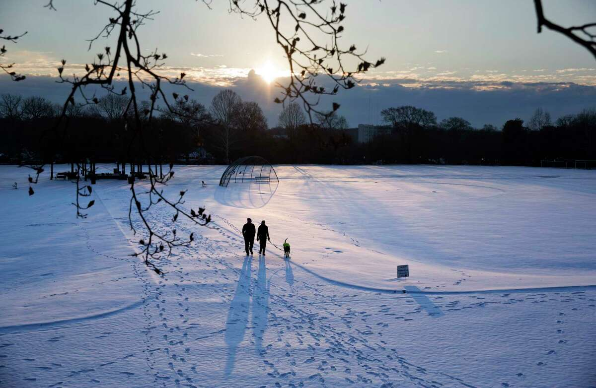 A couple walks their dog through a snow covered Piedmont Park as the sun rises in Atlanta, Wednesday, Jan. 17, 2018. The South awoke on Wednesday to a two-part Arctic mess. First came a thin blanket of snow and ice, and then came the below-zero wind chills and record-breaking low temperatures in New Orleans and other cities.