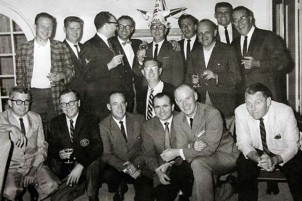 """""""Beetle Bailey"""" creator Mort Walker keeps this photo on his desk in Stamford from his 40th birthday in 1963. Walker is wearing a hat made by """"Hagar the Horrible"""" creator Dik Browne (directly below Walker), and surrounded by cartoonists, including Jerry Dumas (fourth from left in bottom row)."""