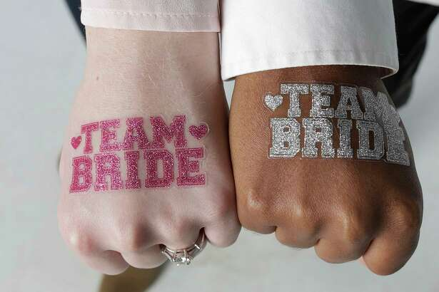 "A glittery ""Team Bride"" tattoo sets a festive tone for any wedding celebration."