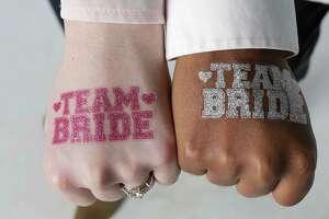 "A glittery ""Team Bride"" tattoo sets a festive tone for any wedding celebration."