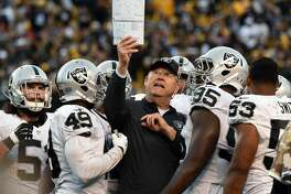 PITTSBURGH, PA - NOVEMBER 8:  Special teams coordinator Brad Seely of the Oakland Raiders shows a play chart to Ben Heeney (L), Jamize Olawale #49, Benson Mayowa #93, Malcolm Smith #53 and other players during a game against the Pittsburgh Steelers at Heinz Field on November 8, 2015 in Pittsburgh, Pennsylvania. The Steelers defeated the Raiders 38-35. (Photo by George Gojkovich/Getty Images)