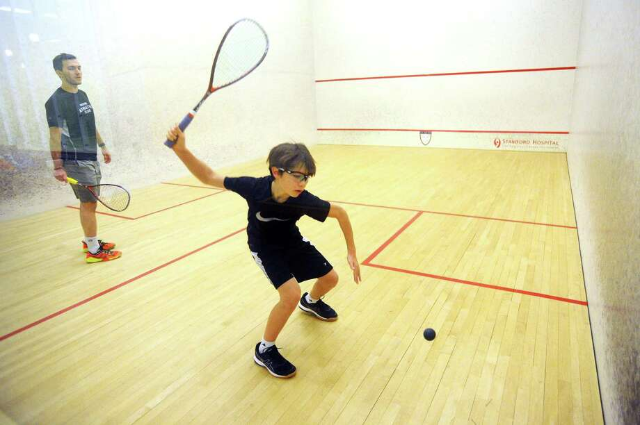 Marcus Ashcraft, 12, lines up a shot under the watchful eye of squash pro Rei Hergeth during a lesson inside Chelsea Piers on Blachley Road in Stamford. Photo: Michael Cummo / Hearst Connecticut Media / Stamford Advocate
