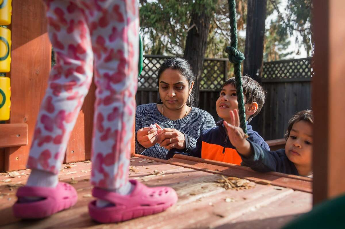 Renuka Sivarajan cleans the hands of Zayne, 2, while other children play on a jungle gym Wednesday, Jan. 17, 2018 at Simply Childhood Day Care center in her home in Fremont, Calif.