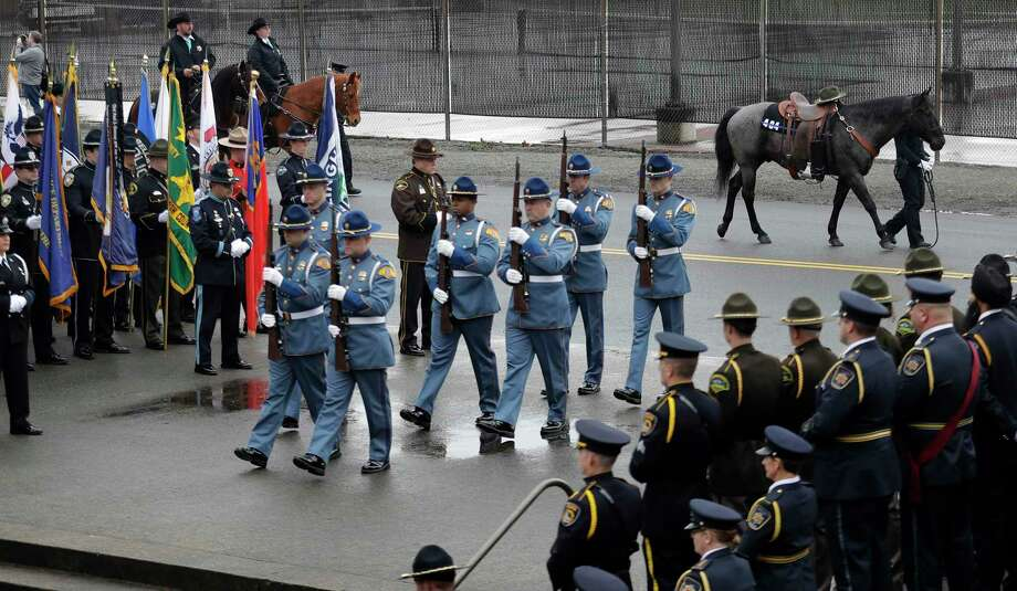 A Washington State Patrol honor guard and the traditional riderless horse take part in a procession for slain Pierce County Sheriff's Deputy Daniel McCartney, Wednesday, Jan. 17, 2018, prior to a memorial service at Pacific Lutheran University in Tacoma, Wash. McCartney died the night of Sunday, Jan. 7, 2018, after being shot while responding to a to a break-in call southeast of Tacoma. Photo: Ted S. Warren, AP / Copyright 2018 The Associated Press. All rights reserved.