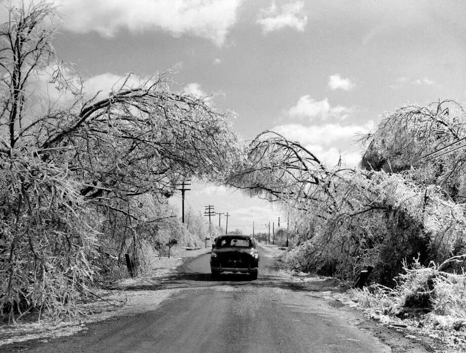 "From the Feb. 2, 1951, Houston Chronicle: ""A bough of ice-laden branches formed this unusually beautiful scene on old Post Oak Road as the sun came out Thursday afternoon.to comfort the outdoors and create a dazzling picture with a sparkle like diamonds. The scene was duplicated all over the county. The heavy ice on the branches bent them to form a complete arbor.""""Old Post Oak Road''? A 1953 street directory indicates that Post Oak Lane was once called that, though published materials from the 1960s note an Old Post Oak Road farther south in Bellaire. Photo: Jess Gibson, Houston Chronicle"