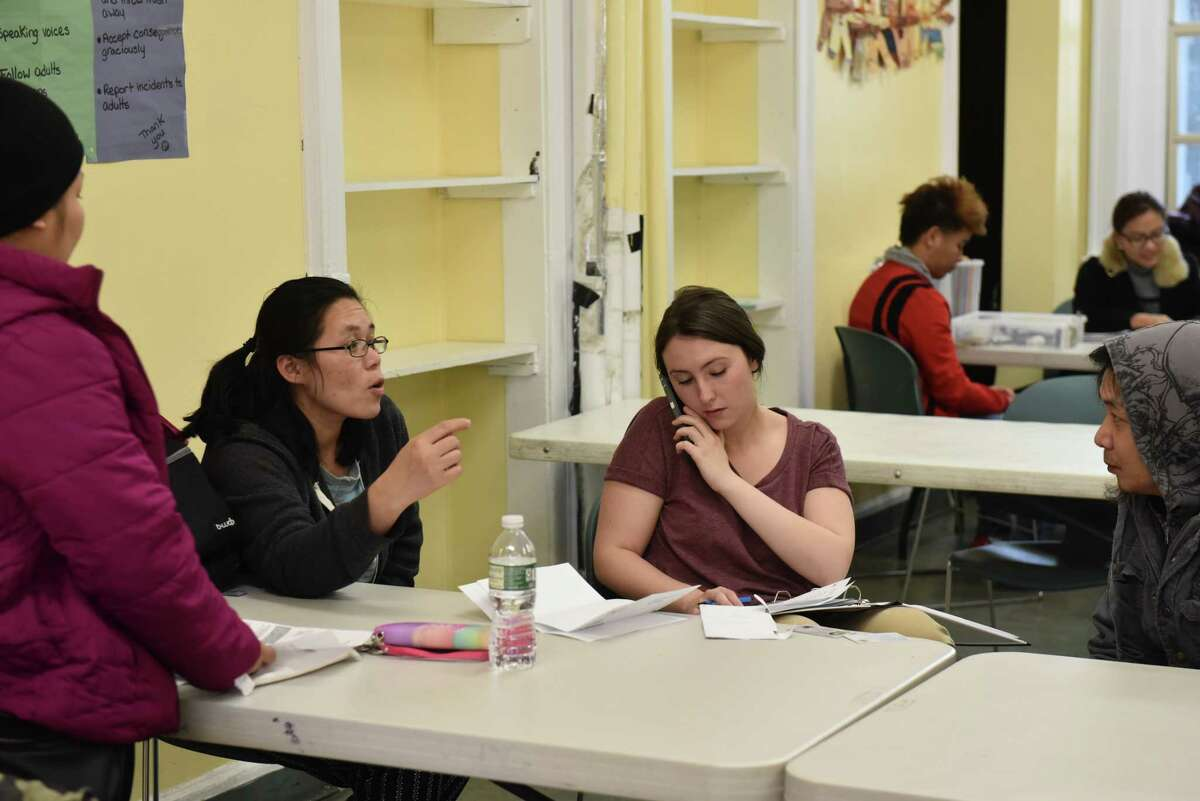 Refugee Community Health Partnership Program coordinator Claire Thompson relays a refugee's medical information over the phone as a worker translates for the refugee ina classroom at Trinity Alliance on Jan. 17, 2017 during an RCHPP Quick Help session. (Massarah Mikati/Times Union)