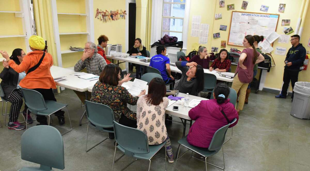 Refugees and Refugee Community Health Partnership Program workers and volunteers gather at a classroom at Trinity Alliance on Jan. 17, 2018 during an RCHPP Quick Help session. (Massarah Mikati/Times Union)