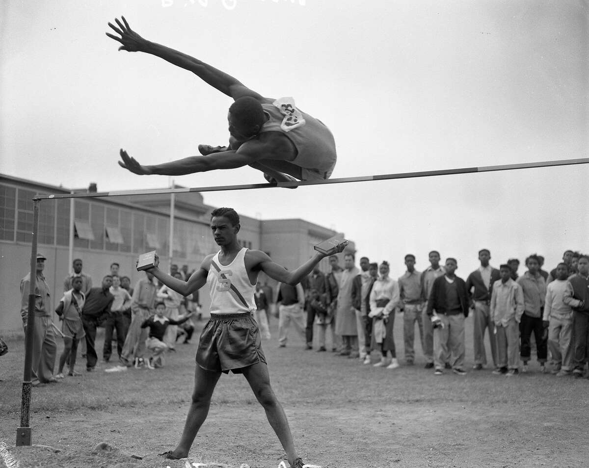 USF's Bill Russell, the biggest and best high jumper in the city of San Francisco, leaps over a very serious John Mathis, the smallest and second best. Russell, who stands 6-feet 9-inches, has a personal best of 6 feet 7 and 1/2 inches. Mathis, who is only 5-feet 7-inches tall, has compiled an amazing record at San Francisco State. Although only a freshman, he is eligible for varsity competition and has been defeated only once this year--that by Herm Wyatt, a great leaper from San Jose State and Fort Ord. Mathis' best is 6-3, and he won the Far Western varsity title at 6 feet 2 and 3/4 inches. In this picture, Russell floats easily over 6-1 as Mathis counteracts nervousness by holding a book in each hand. Both jumpers will compete in the Modesto Relays. Published May 22, 1954. Johnny Mathis
