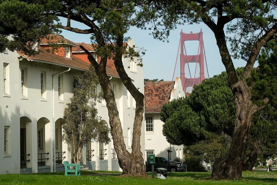 The Golden Gate Bridge rises behind buildings at Fort Scott in the Presidio. The Presidio Trust is seeking a do-gooding organization with ample resources to develop the area. Photo: Noah Berger, Special To The Chronicle