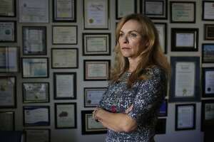 Rose Padilla Johnson, chief executive officer of Davis Street,  stands for a portrait in front of a wall of awards and other commendatios for Padilla Johnson at Davis Street on Wednesday, January 17, 2018 in San Leandro, Calif.