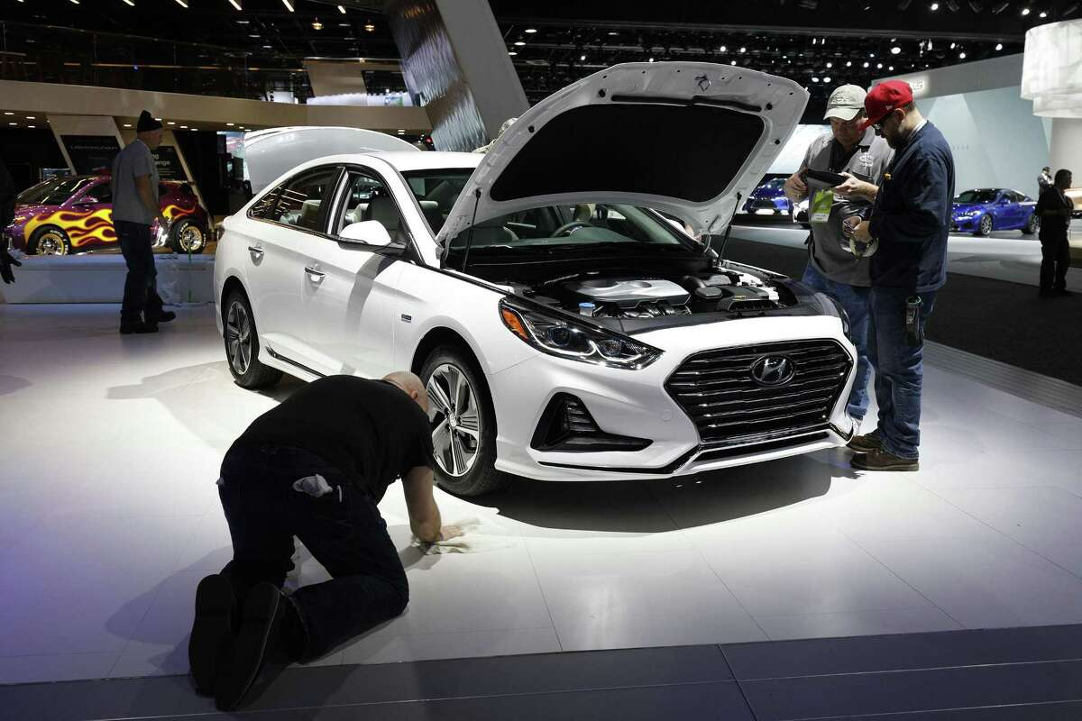 Workers prep around a Hyundai Sonata at the Hyundai 1272exhibit is shown at the 2018 North American International Auto Show January 16, 2018 in Detroit, Michigan. More than 5,100 journalists from 61 countries attend the NAIAS each year. The show opens to the public January 20th and ends January 28th.