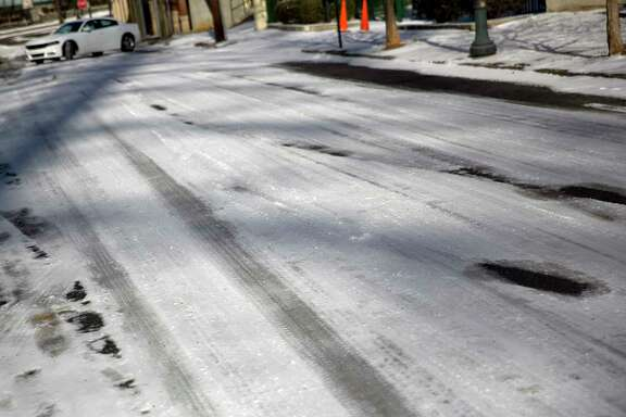 Ice covers a street as a car struggles to climb a hill in Atlanta, Wednesday, Jan. 17, 2018. The South awoke on Wednesday to a two-part Arctic mess. First came a thin blanket of snow and ice, and then came the below-zero wind chills and record-breaking low temperatures in New Orleans and other cities. (AP Photo/David Goldman)