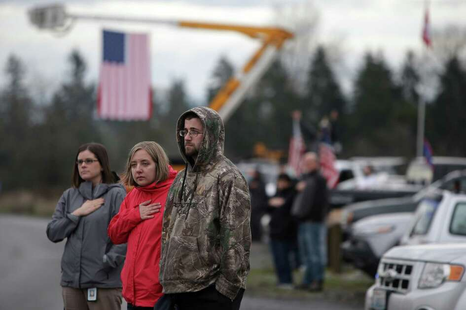 People stand along the route as the funeral procession for Pierce County sheriff's deputy Daniel McCartney, who was killed in the line of duty, passes by, Wednesday, Jan. 17, 2018. Three thousand people were expected at his memorial service.