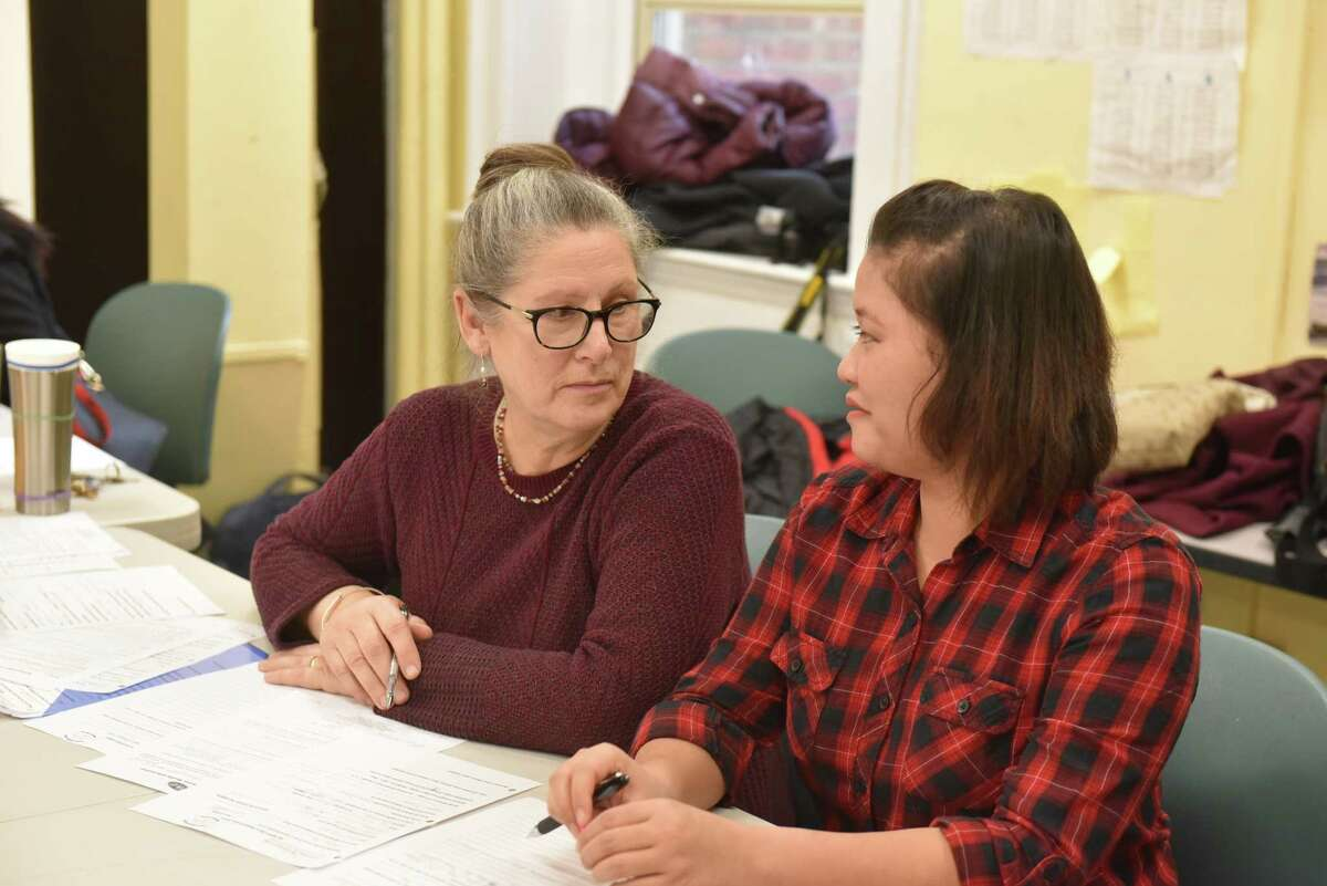 Refugee Community Health Partnership Program co-founder Susan Kukuk converses with refugee community outreach worker Paw Shee Wah in a classroom at Trinity Alliance on Jan. 17, 2017 during an RCHPP Quick Help session. (Massarah Mikati/Times Union)