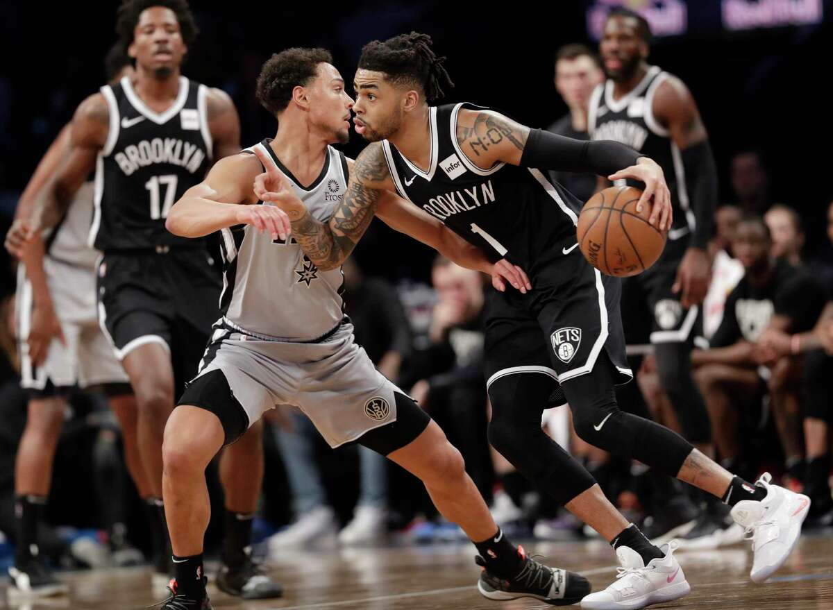 Brooklyn Nets guard D'Angelo Russell (1) drives around San Antonio Spurs guard Bryn Forbes (11) during the first half of an NBA basketball game, Monday, Feb. 25, 2019, in New York. (AP Photo/Kathy Willens)