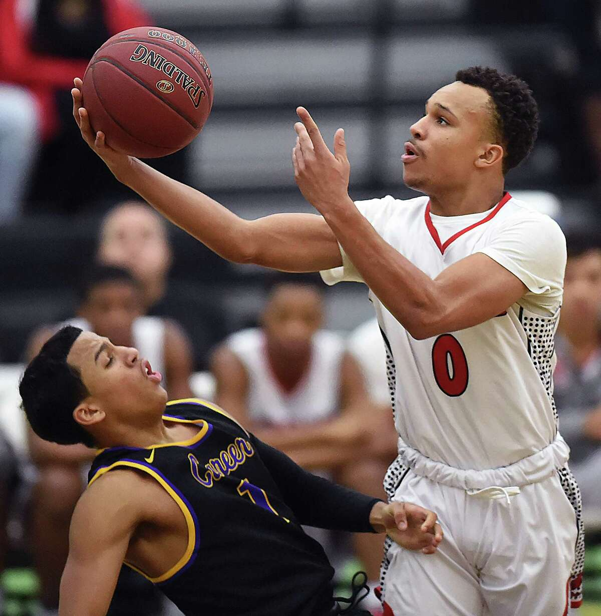 Wilbur Cross' Twane Taylor elevates for a shot against Career's Kyle Daniels, Wednesday, Jan. 17, 2018, at Floyd Little Athletic Center in New Haven. Taylor was called for an offensive charge. Wilbur Cross won, 57-50.