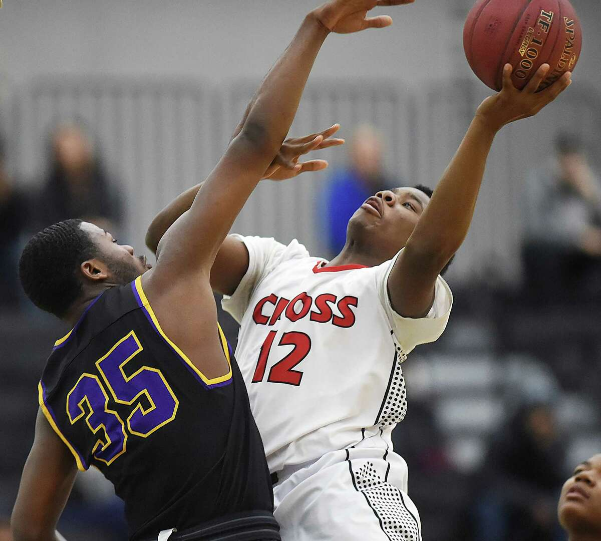 Wilbur Cross' Terrence Edwards elevates for a shot as Career's Jalen Jones defends, Wednesday, Jan. 17, 2018, at Floyd Little Athletic Center in New Haven. Wilbur Cross won, 57-50.