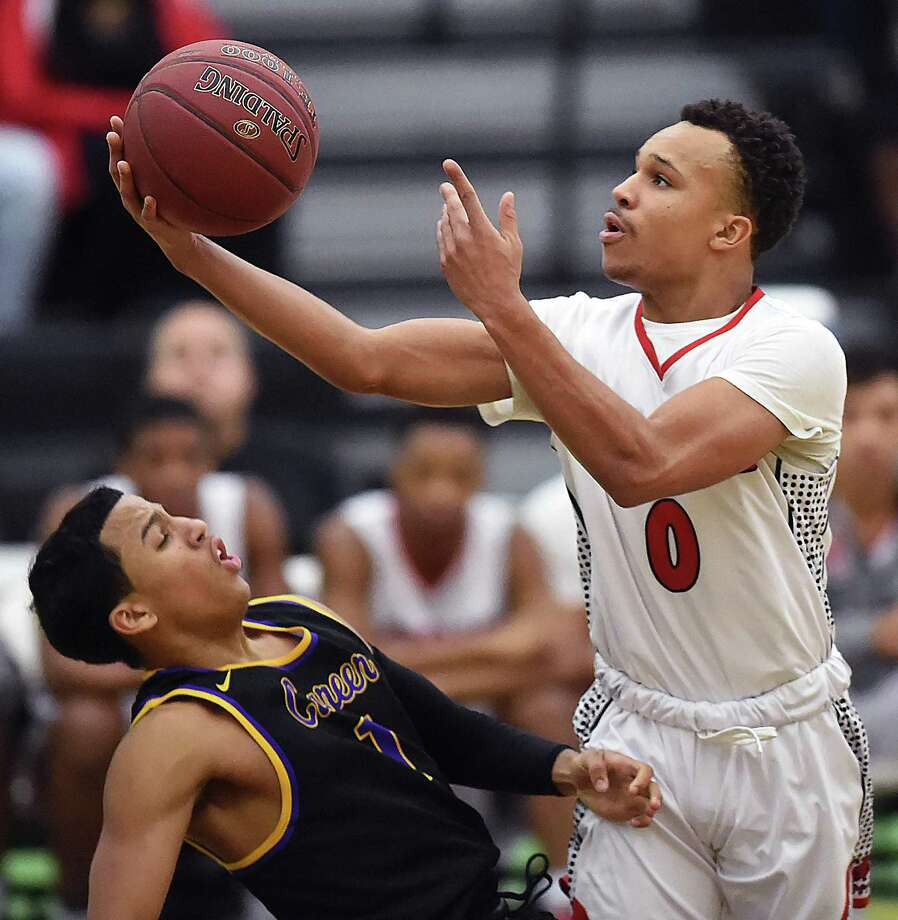 Wilbur Cross' Kwane Taylor elevates for a shot against Career's Kyle Daniels on Wednesday at Floyd Little Athletic Center in New Haven. Wilbur Cross won 57-50. Photo: Catherine Avalone / Hearst Connecticut Media / New Haven Register