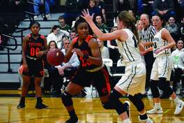 Edwardsville senior forward Myriah Noodel-Haywood (No. 23) dribbles the ball near the free-throw line with a St. Joseph's defender guarding her in the second quarter of Wednesday's non-conference game.