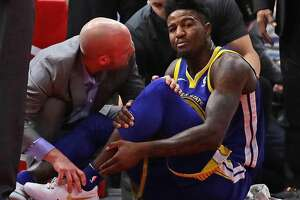 CHICAGO, IL - JANUARY 17:  Jordan Bell #2 of the Golden State Warriors is attended to after suffering a leg injury on the first play of the game against the Chicago Bulls at the United Center on January 17, 2018 in Chicago, Illinois. NOTE TO USER: User expressly acknowledges and agrees that, by downloading and or using this photograph, User is consenting to the terms and conditions of the Getty Images License Agreement.  (Photo by Jonathan Daniel/Getty Images)