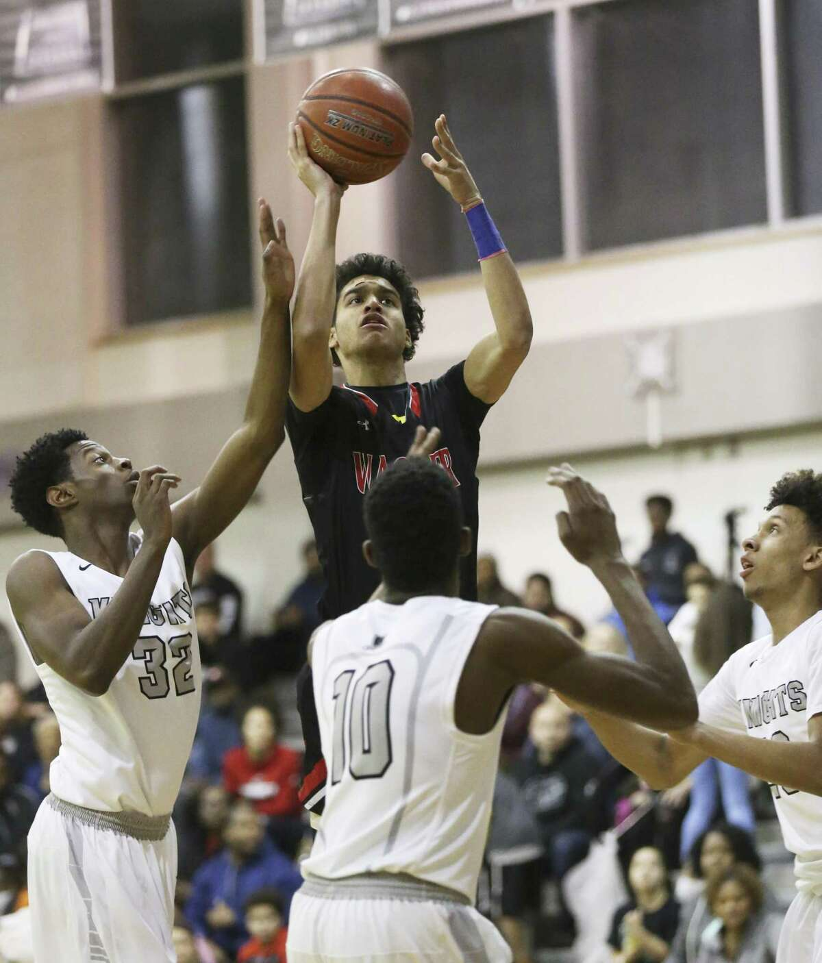 Wagner's DaRaun Clark (11) shoots over a trio of Steele defenders in 27-6A boys basketball on Wednesday, Jan. 17, 2018. Wagner defeated Steele, 71-63. (Kin Man Hui/San Antonio Express-News)