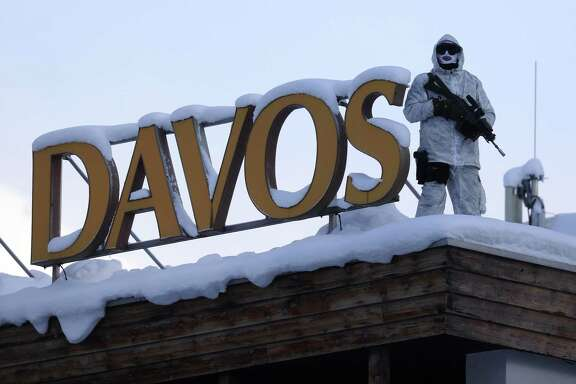 An armed member of the Swiss police watches from the roof of the Hotel Davos ahead of last year's World Economic Forum in Davos, Switzerland.