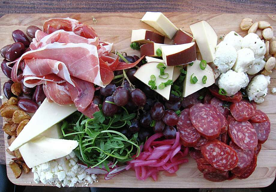 A charcuterie board with cheeses, salami, prosciutto, olives, fried garlic and more from The Point on N. Main. Photo: Mike Sutter /San Antonio Express-News