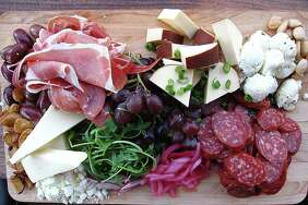 A charcuterie board with cheeses, salami, prosciutto, olives, fried garlic and more from The Point on N. Main.