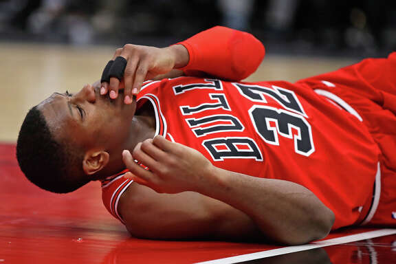Kris Dunn #32 of the Chicago Bulls lays on the floor after suffering a mouth injury following a dunk against the Golden State Warriors at the United Center on January 17, 2018 in Chicago, Illinois. The Warriors defeated the Bulls 119-112.