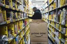 FILE - In this Wednesday, Dec. 20, 2017, file photo, a clerk reaches to a shelf to pick an item for a customer order at the Amazon Prime warehouse, in New York. Amazon announced Thursday, Jan. 18, 2018, that it has narrowed down its potential site for a second headquarters in North America to 20 metropolitan areas, mainly on the East Coast. (AP Photo/Mark Lennihan, File)