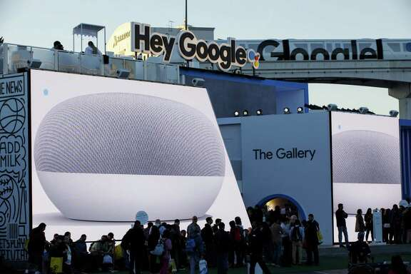 Alphabet Inc.'s Google Home Mini smart speakers are displayed on screens as attendees stand in line to enter the company's exhibit at the 2018 Consumer Electronics Show (CES) in Las Vegas, Nevada, U.S., on Thursday, Jan. 11, 2018. Electric and driverless cars will remain a big part of this year's CES, as makers of high-tech cameras, batteries, and AI software vie to climb into automakers' dashboards. Like many of the world's largest internet companies in recent years, Google has begun relying on machine learning — computer algorithms that can learn tasks on their own by analyzing large amounts of data.