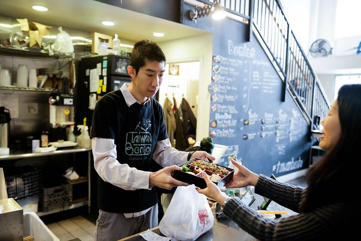 Owner Willy Tang (left) gives a dish to a customer at Taiwan Bento in Oakland, Calif., on Thursday, Jan. 4, 2018.