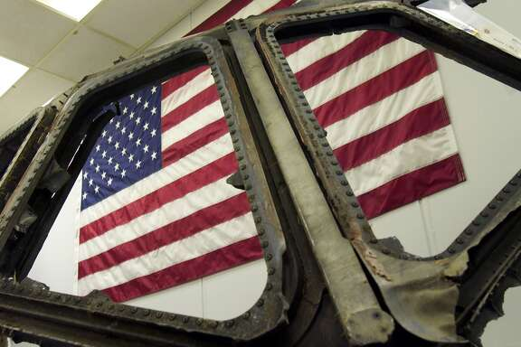 KENNEDY SPACE CENTER, FLORIDA - JANUARY 30: A U.S. flag hangs behind the cockpit windows from the Space Shuttle Columbia January 30, 2004 at Kennedy Space Center in Florida. The remnents, which were open to the news media on January 30, will be stored on the 16th floor and will be available for research. (Photo by Matt Stroshane/Getty Images)