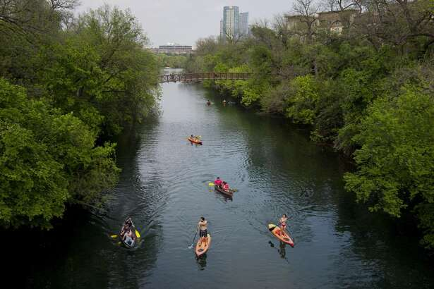 People in canoes and on paddleboards move down Barton Creek in Austin, Texas, on April 3, 2015.