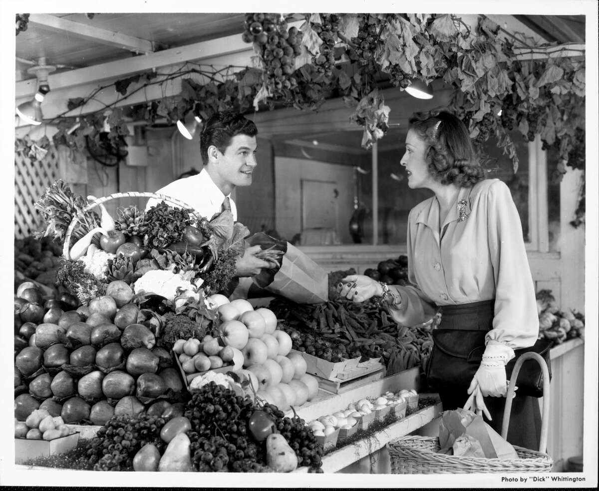 A grocer helps a shopper in a California market in the 1940s.