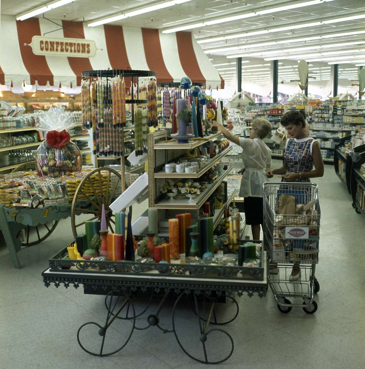 A view of shoppers as they look at candles on a display cart in a newly opened Piggly Wiggly supermarket in Encino, California, 1962.