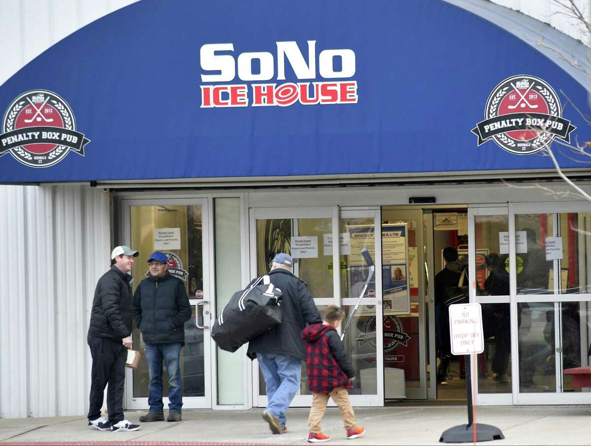 Parents and players enter the SoNo Ice House in Norwalk on Tuesday. Teammates and coaches of 10-year-old Nico Mallozzi, who died of complications from the flu on Sunday, met privately with a grief counselor.