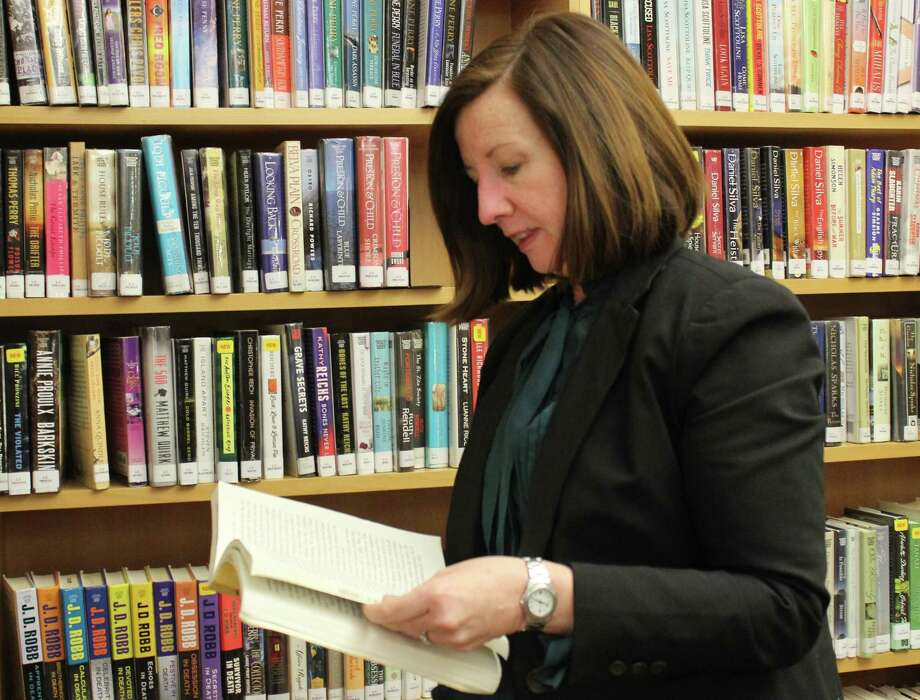 Town Librarian Helene Murtha looks for a book to add to her reading list. Photo: Genevieve Reilly / Hearst Connecticut Media / Fairfield Citizen