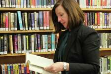 Town Librarian Helene Murtha looks for a book to add to her reading list.