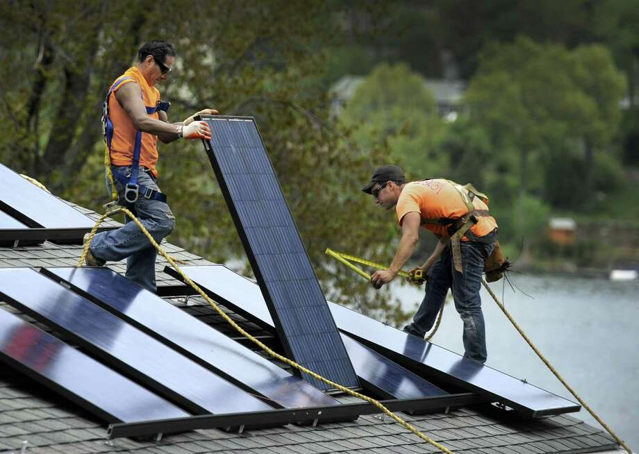 Jose Yuangui, left, and Avi Baron, are part of a crew from Danbury-based Ross Solar Group, LLC that is installing solar panels on a Brookfield, Conn.  home, Tuesday, May 12, 2015. Photo: Carol Kaliff / Carol Kaliff / The News-Times