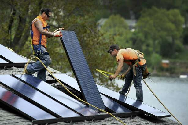 Jose Yuangui, left, and Avi Baron, are part of a crew from Danbury-based Ross Solar Group, LLC that is installing solar panels on a Brookfield, Conn.  home, Tuesday, May 12, 2015.