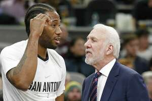 San Antonio Spurs' Kawhi Leonard talks with San Antonio Spurs head coach Gregg Popovich on the bench during first half action against the Denver Nuggets on Saturday at the AT&T Center.