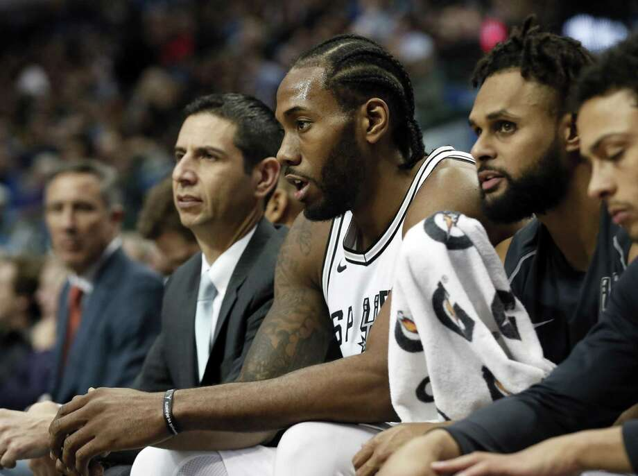FILE - In this Tuesday, Dec. 12, 2017 file photo, San Antonio Spurs' Kawhi Leonard, center, sits on the bench after playing in the first half of an NBA basketball game against the Dallas Mavericks in Dallas. The San Antonio Spurs say Kawhi Leonard will be out indefinitely as he continues his recovery from a leg injury, Wednesday, Jan. 17, 2018. Leonard has played in just nine games after missing the beginning of the season because of right quadriceps tendinopathy. He also was sidelined briefly because of a shoulder injury. (AP Photo/Tony Gutierrez, File) Photo: Tony Gutierrez, STF / Associated Press / Copyright 2017 The Associated Press. All rights reserved.