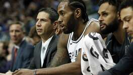 FILE - In this Tuesday, Dec. 12, 2017 file photo, San Antonio Spurs' Kawhi Leonard, center, sits on the bench after playing in the first half of an NBA basketball game against the Dallas Mavericks in Dallas. The San Antonio Spurs say Kawhi Leonard will be out indefinitely as he continues his recovery from a leg injury, Wednesday, Jan. 17, 2018. Leonard has played in just nine games after missing the beginning of the season because of right quadriceps tendinopathy. He also was sidelined briefly because of a shoulder injury. (AP Photo/Tony Gutierrez, File)