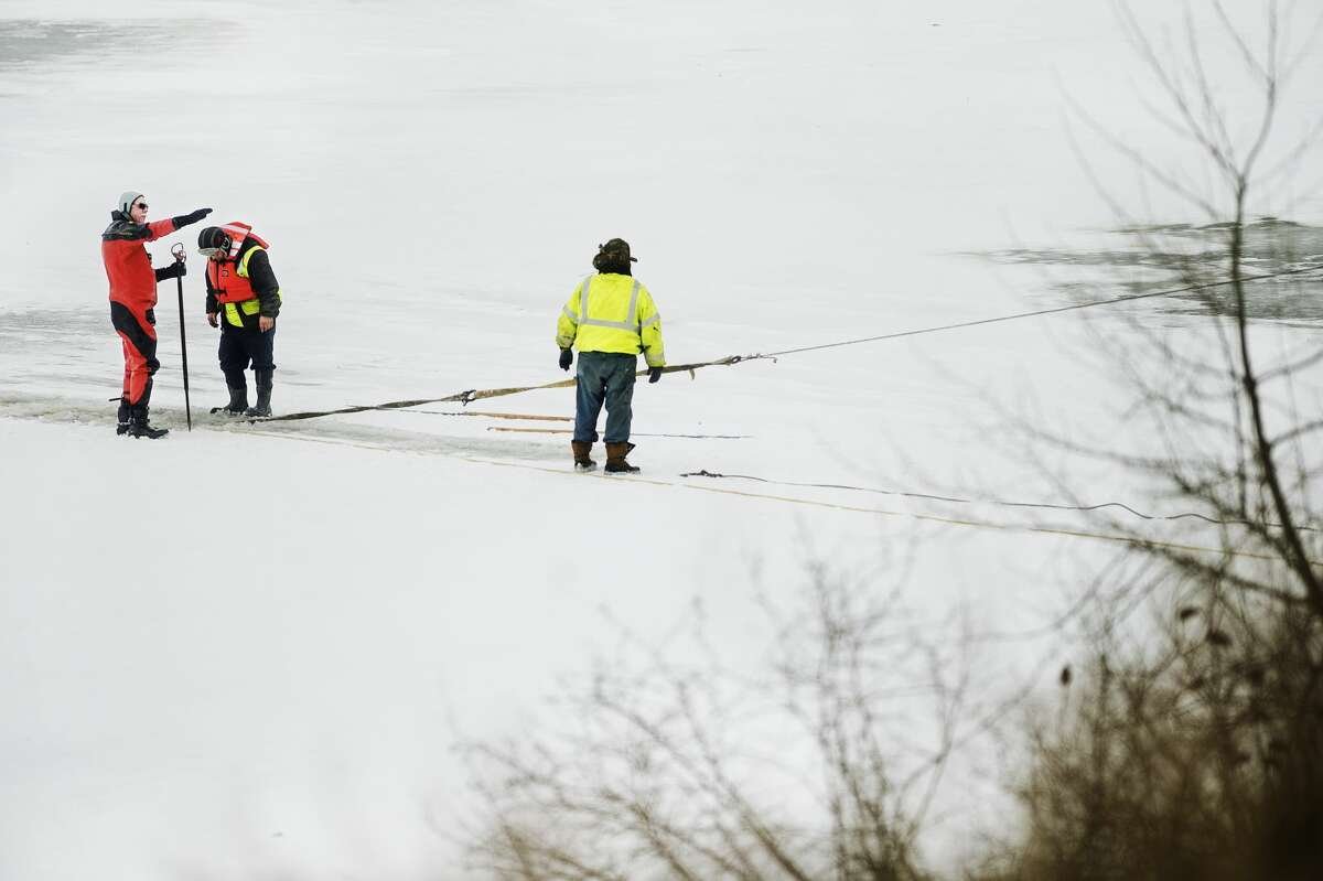 Crews from Cole's Wrecker Service and Mike's Wrecker Service work to remove a submerged vehicle from Sanford Lake on Thursday, Jan. 18, 2018 after a Breckenridge man died after falling through thin ice on Tuesday night. (Katy Kildee/kkildee@mdn.net)