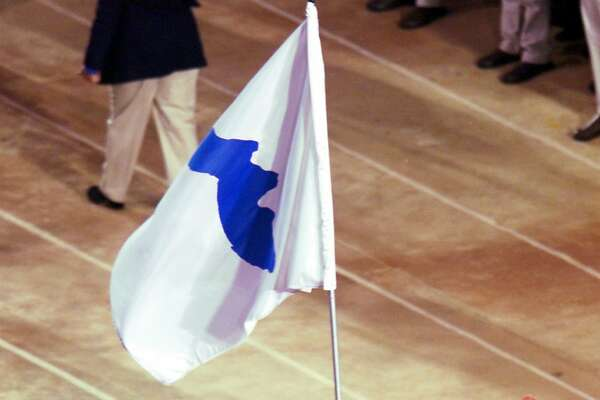 FILE - In this Sept. 15, 2000, file photo, Pak Jung Chul, left, a North Korea's Judo coach, and Chung Eun-sun, a South Korean basketball player, carry a flag representing a united Korea into Olympic Stadium during the Opening Ceremony of the Olympics in Sydney. When athletes of the rival Koreas walked together behind a single flag for the first time since their 1945 division at the start of the Sydney Olympics, it was a highly emotional event that came on the wave of reconciliation mood following their leaders� first-ever summit talks. Eighteen years later, now, the Koreas are pushing to produce a similar drama during the upcoming Pyeongchang Olympics. But they haven�t generated as much enthusiastic supports as they had both at home and abroad. (AP Photo/Rusty Kennedy, File)