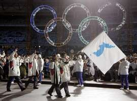 FILE - In this Feb. 10, 2006, file photo, Korea's flag-bearers Bora Lee and Jong-In Lee, carrying a unification flag lead their teams into the stadium during the 2006 Winter Olympics opening ceremony in Turin, Italy. When athletes of the rival Koreas walked together behind a single flag for the first time since their 1945 division at the start of the 2000 Sydney Olympics, it was a highly emotional event that came on the wave of reconciliation mood following their leaders� first-ever summit talks. Eighteen years later, now, the Koreas are pushing to produce a similar drama during the upcoming Pyeongchang Olympics. But they haven�t generated as much enthusiastic supports as they had both at home and abroad. (AP Photo/Amy Sancetta, File)