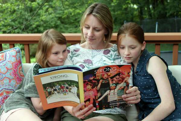 """Sarah Beach and her daughters Daisy and Lucy look at the prototype of her magazine, """"STRONG."""" at their home in Wilton."""