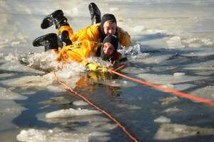 Milford firefighters C.J. Staiger, top, and Tom Sarno practice cold water ice rescue techniques with the Milford Fire Department on Milford Harbor on Thursday, January 18, 2018.