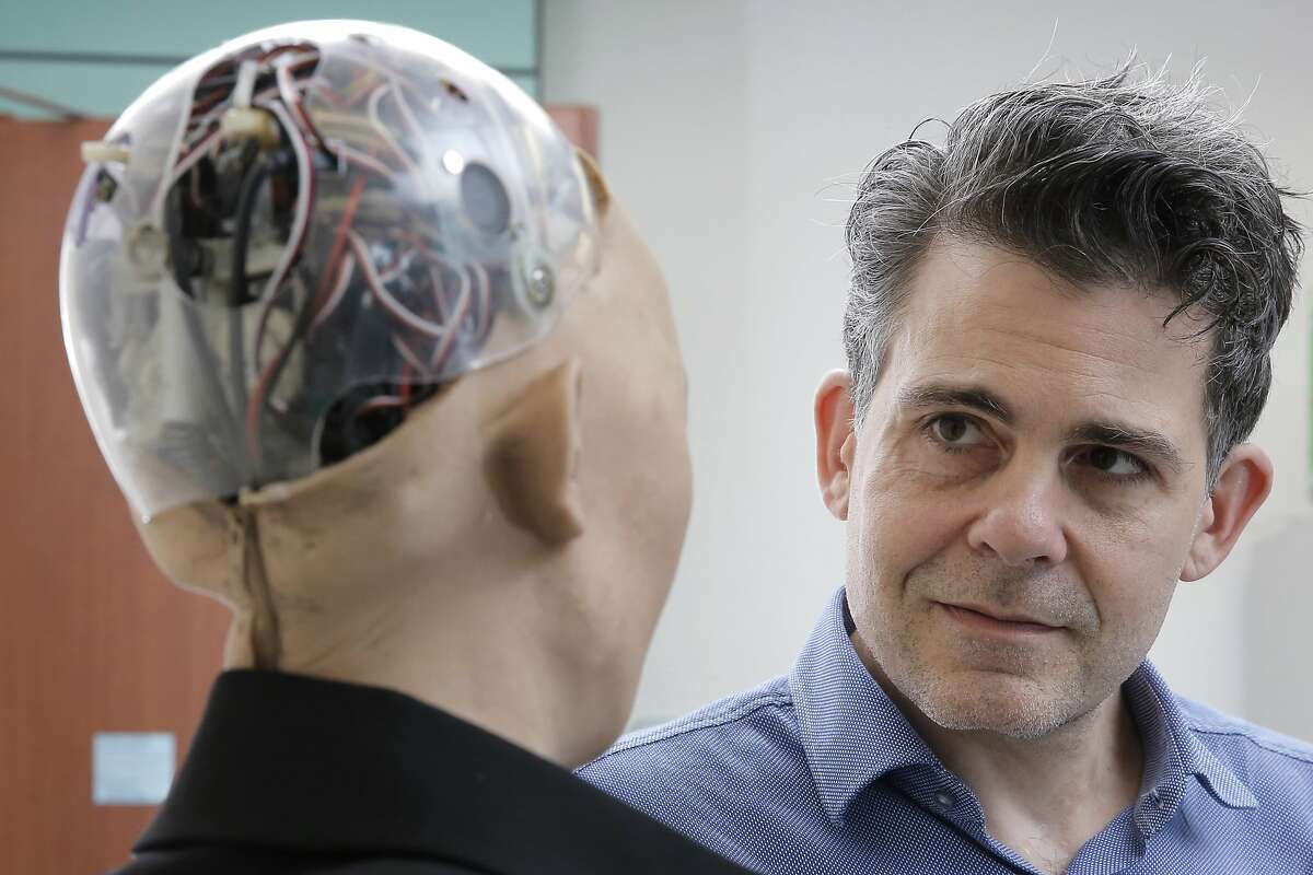 In this Sept. 28, 2017, photo, David Hanson, the founder of Hanson Robotics, talks with his company's flagship robot Sophia, a lifelike robot powered by artificial intelligence in Hong Kong. Sophia is a creation of the Hong Kong-based startup working on bringing humanoid robots to the marketplace. Hanson envisions a future in which AI-powered robots evolve to become �super-intelligent genius machines� that can help solve mankind�s most challenging problems. (AP Photo/Kin Cheung)